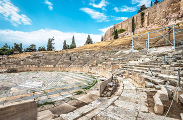 Fototapete - Ancient Greek ruins at the foot of Acropolis, Athens, Greece. Panorama of Theatre of Dionysus in summer. It is one of top landmarks in Athens. View to famous remains of the old Athens city.