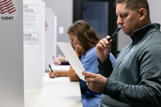 Election: Man Thinking About Who To Vote For On Ballot