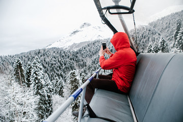 Man on chairlift taking photo of nature