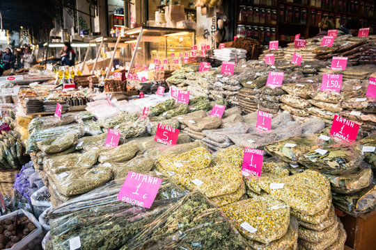 Stands with camomile, oregano and other herbs and spices with pink price tags on the Central Market of Athens.