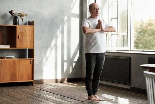 Sporty senior hispanic man working out, yoga in basic standing asana tadasana, mountain yoga posture at home.