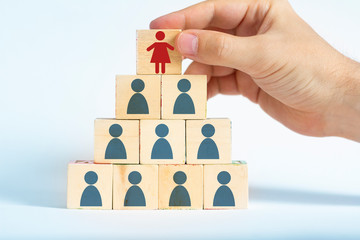 human resources manager is selecting a female worker atop a pyramid made out of male employee icons