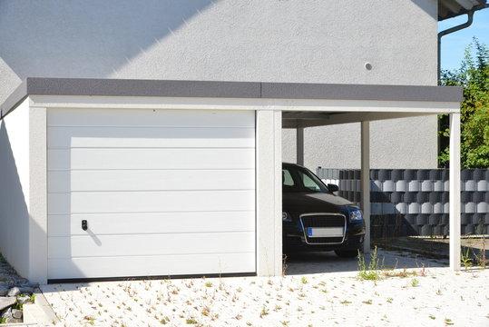 Moderne Beton-Garage mit Automatik-Tor und angebautem Carport in der Hauszufahrt