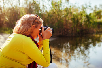 Middle-aged woman checking images on camerasitting by autumn river bank. Senior woman enjoying hobby