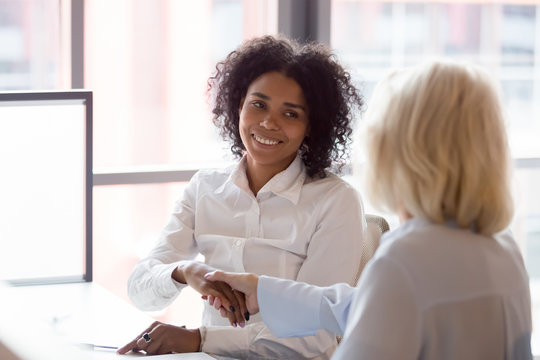 Smiling african American employee handshake colleague greeting at workplace