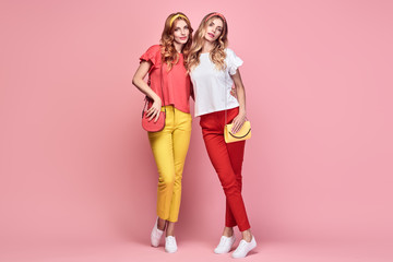 Fashionable embracing woman sisters smiling on pink background. Two Shapely Girl Having Fun dance, Trendy yellow coral summer outfit, fashion hairstyle, makeup. Gorgeous female model, funny concept Wall mural