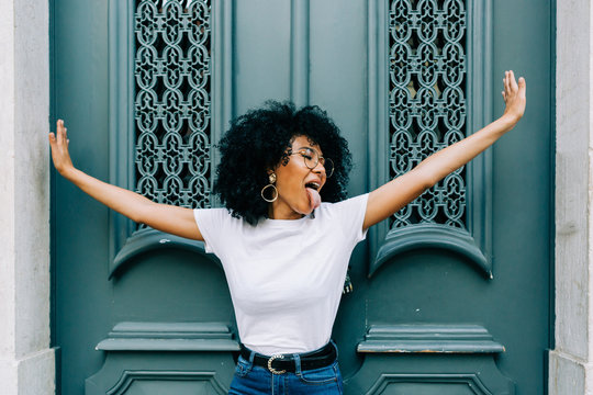 Young African American woman standing with closed eyes by green wooden door and sticking out tongue on daytime