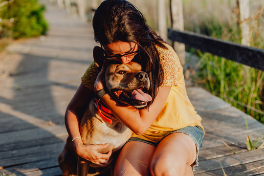 Happy adult woman hugging dog at countryside