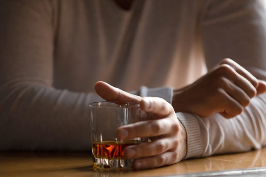 Close up man holding glass with alcohol in hand, drinking alone