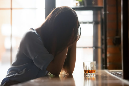Lonely unhappy woman sitting alone with glass of alcohol