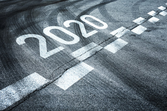 2020 year number written on asphalt road with tire lines.