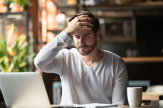 Upset man working in cafe, suffering from headache, touching forehead