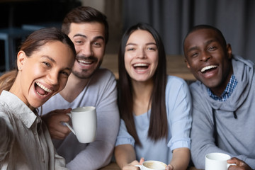 Head shot portrait of smiling diverse friends sitting in cafe together