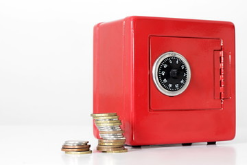saving money in a red money box with stack of coins white background no people stock image and stock photo
