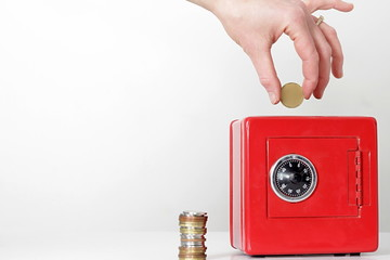 saving money in a red money box with hand white background with people stock image stock photo