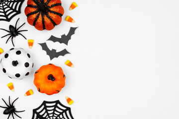 Halloween side border of pumpkins, candy and decor. Flat lay over a white background with copy space.