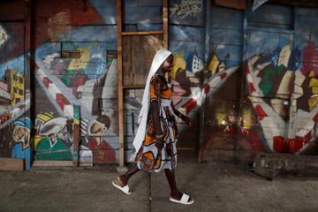 A girl walks  beside her house in Medina neighbourhood, Dakar,