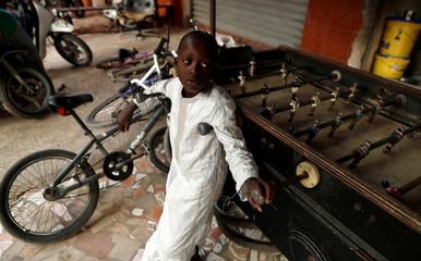 A boy leans against a babyfoot table in Medina neighbourhood, Dakar,