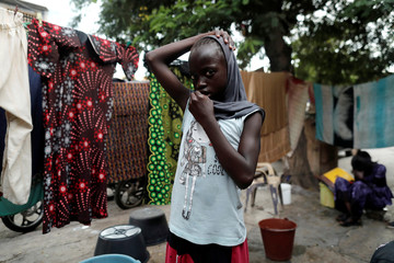 A girl is pictured beside clothes hung up to dry outside her house in Medina neighbourhood, in Dakar