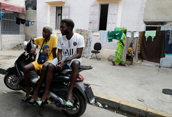 People sit on a motocycle in Medina neighbourhood, in Dakar