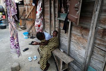 A girl reacts as she carries her sister in Medina neighbourhood, Dakar