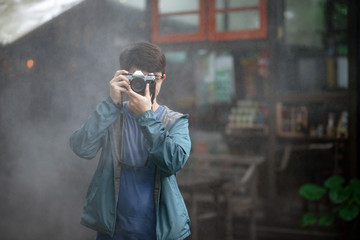 Asian male photographer holding film camera with fog