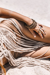 close up of beautiful young woman in boho style bikini lying on sand at the beach