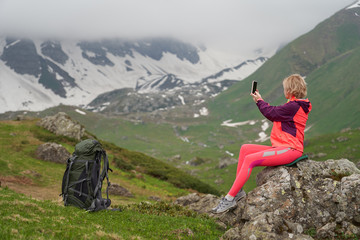 Portrait of woman taking a picture at the beautiful mountains background.