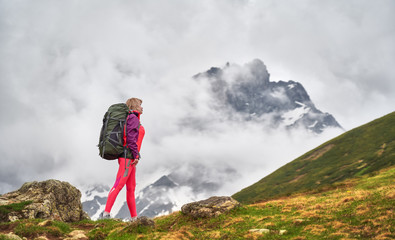 Portrait of hiker with a backpack at the beautiful mountains background.