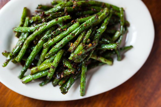 Spicy Szechuan Green Beans on white plate and wood surface