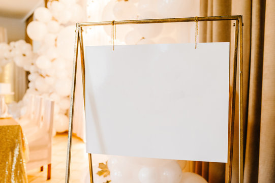 Frame. Place for text. White paper in gold frame. Easel. Luxury style elegant wedding decor for the ceremony.