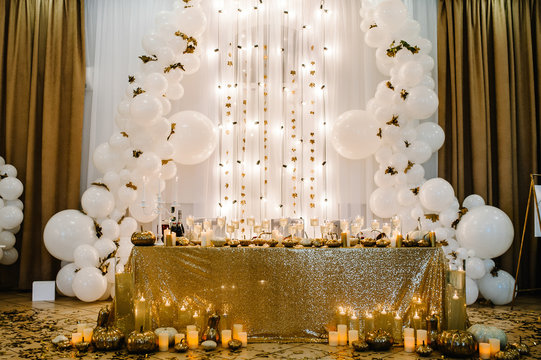 Table setting for wedding. Decorated arch for wedding ceremony. White balloons, candles, autumn leaves and small pumpkins. Autumn location and Halloween decor.