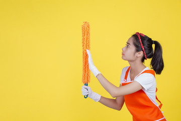 Cleaning concept. A beautiful woman with a cleaning device on a yellow background.
