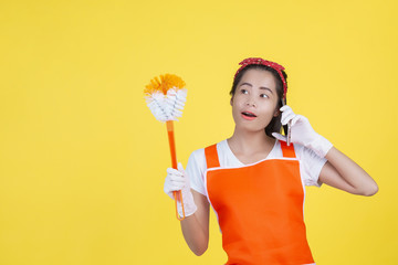 Cleaning concept. Beautiful woman holding a toilet flushing brush and phone on a yellow background.