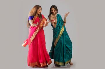 young women dancing in saree