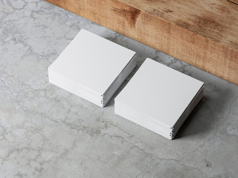 Stacks of white square paper sheets mockup on concrete floor