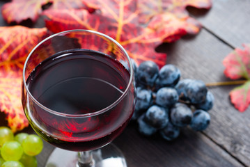 glass of red wine and grapes on black wooden table background
