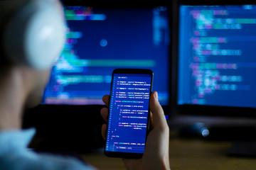 Software developer freelancer with white headphones and glasses working with program code: C++ Java, Javascript on wide displays and smartphone at night. Develops new web, desktop, mobile application.