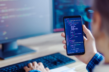 Closeup freelancer hand is holding smartphone with program code. Programmer developer is writing...