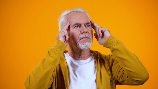 Senior male telepathist touching temples, trying to read thoughts, mentalist