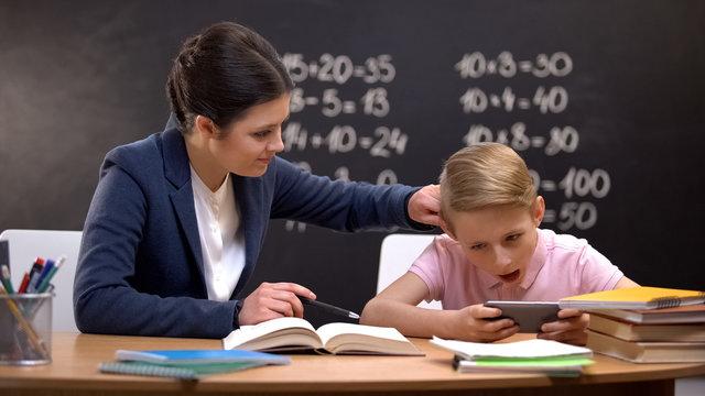 Irritated lady teacher grabbing boys playing on smartphone ear, punishment