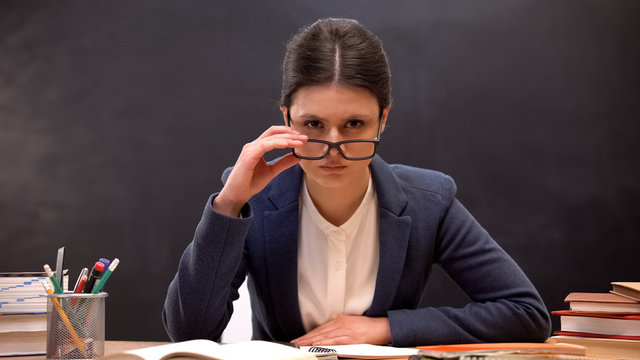 Angry teacher looking aggressively to camera taking off glasses, strict lecturer