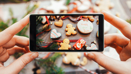Festive culinary blog. Closeup of lady hands using smartphone to take picture of Christmas handmade gingerbread cookies.