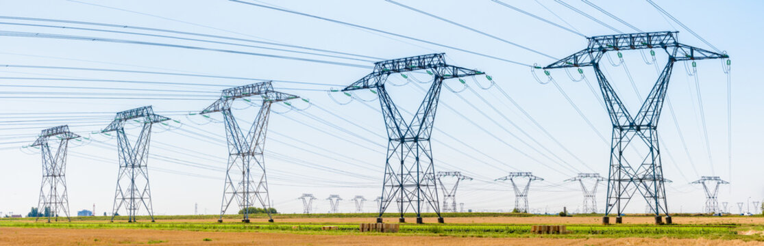 Panoramic view of a row of electricity pylons next to a road in the french countryside with dozens of other pylons in the distance under a clear blue sky.