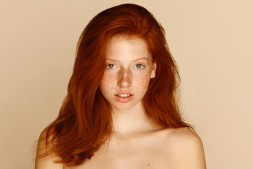 Freckles young girl close up portrait. Attractive model with beautiful natural ginger red hair