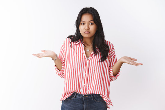 Confused insecure female newbie standing clueless shrugging and spread hands sideways in dismay and frustration being unaware and uncertain how mistake happened against white background