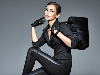 Beautiful woman in black  holds fashion handbag Wall mural
