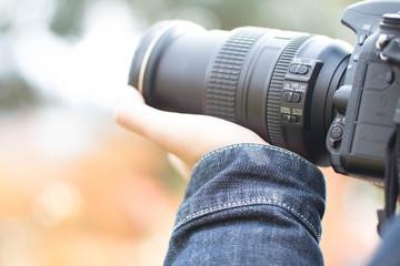 カメラを構えて紅葉の写真を撮る男性の手元