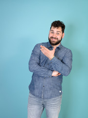 cool and young man with black hair and black beard posing in front of blue background doing...