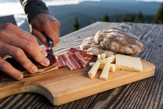 Man slice up delicious South Tyrolean smoked bacon and cheese with flat bread lying on a rustic table